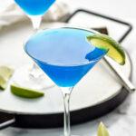 two martini glasses of blue daiquiri with fresh lime wedge garnish
