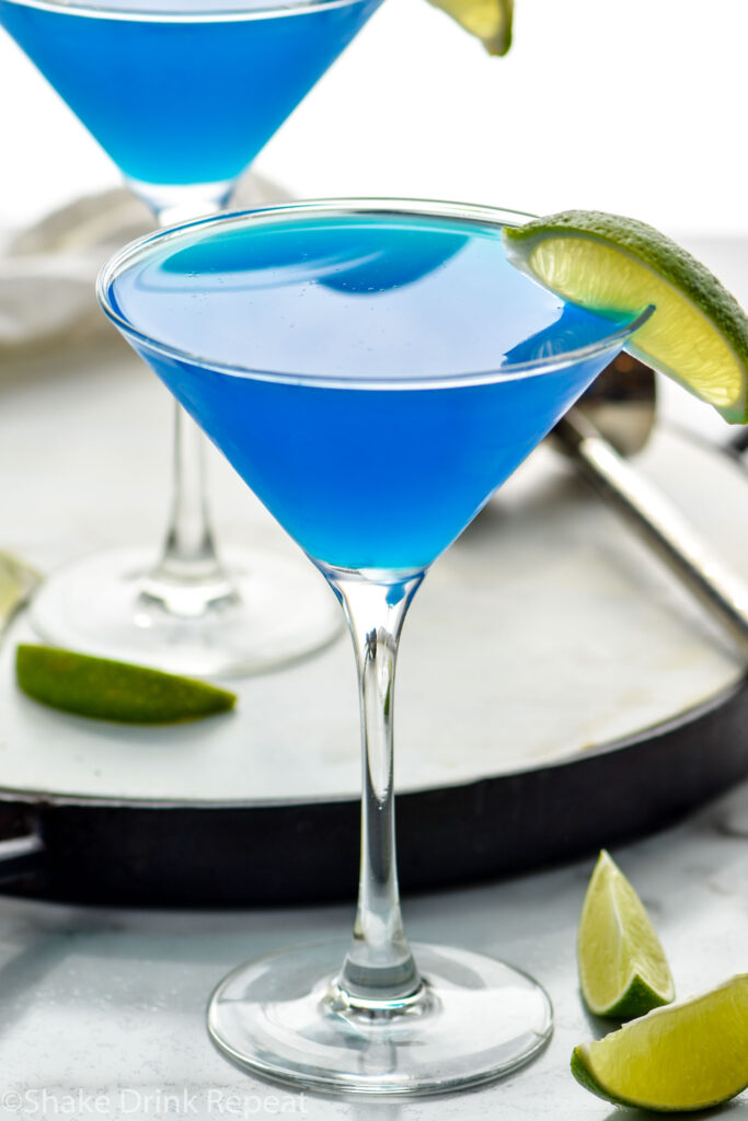 two martini glasses of blue Daiquiri with fresh lime wedges for garnish