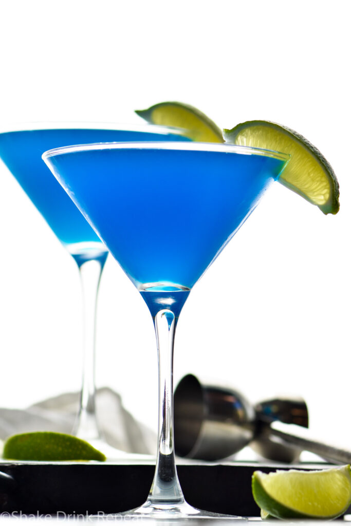 two martini glasses of blue daiquiri with fresh lime wedges