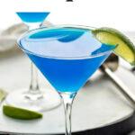 martini glass of blue daiquiri with fresh lime wedge