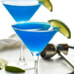 two martini glasses of blue daiquiri with fresh lime wedge garnish and jigger in background