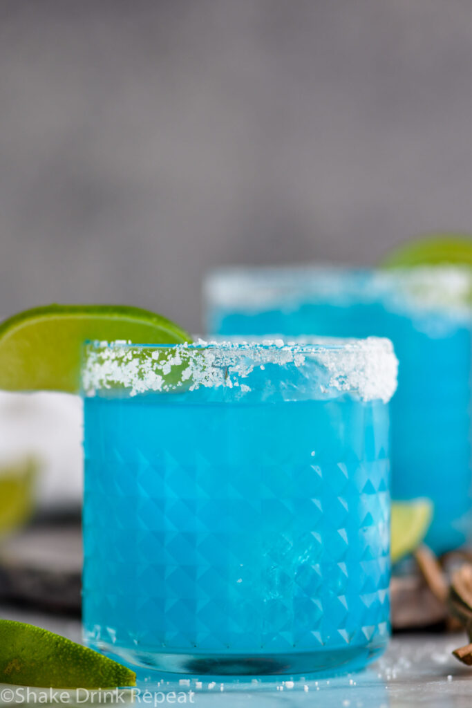 two glasses of blue margarita with salted rim and lime wedge garnish