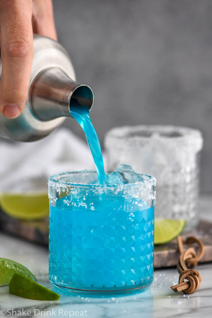 man pouring blue margarita from a shaker into a glass with ice, salted rim and fresh lime wedges