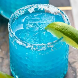 two glasses of blue margarita with salted rims, ice, and fresh lime wedge