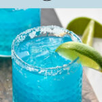 Glass of Blue Margarita with ice, salted rim, and fresh lime wedge