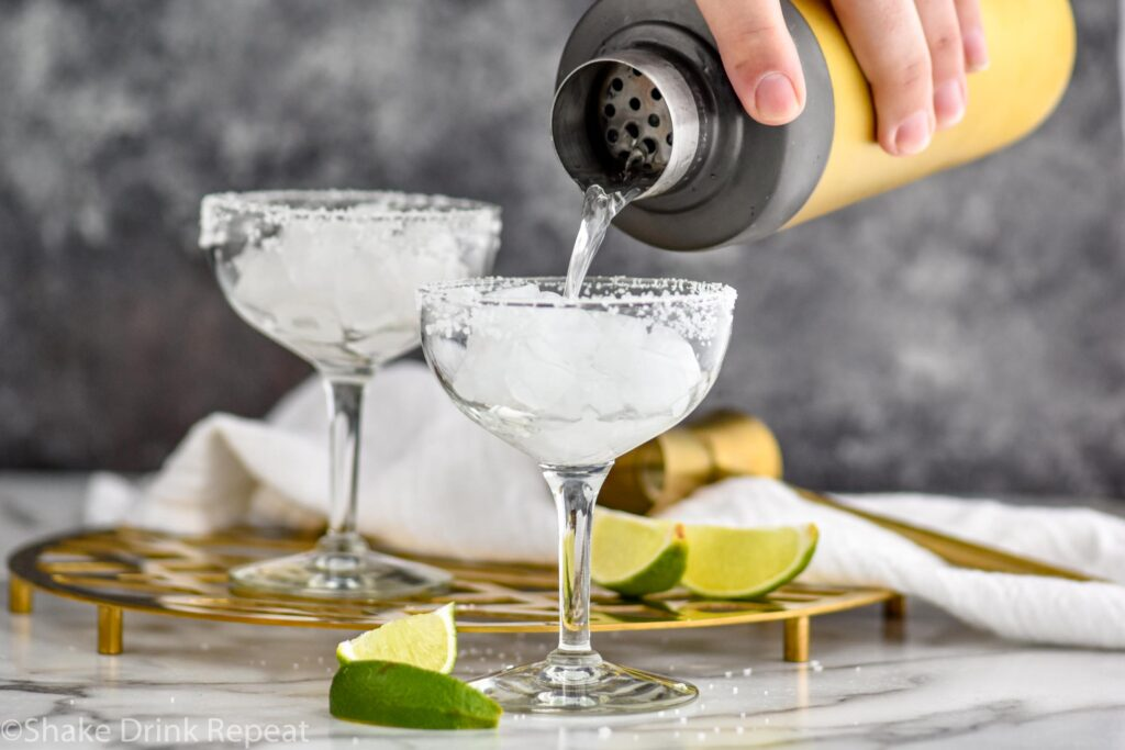 Man's hand pouring shaker of Cadillac Margarita ingredients into a margarita glass with salted rim filled with ice and surrounded by lime wedges