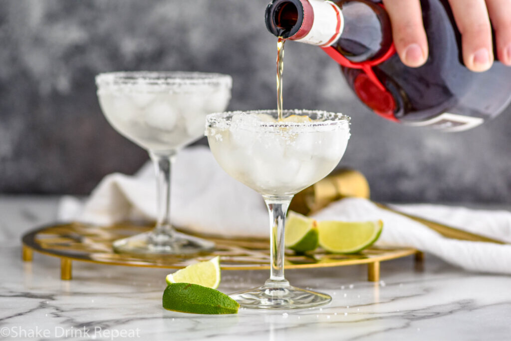 man pouring Grand Marnier into a glass of cadillac margarita with ice, salted rim, and lime wedges