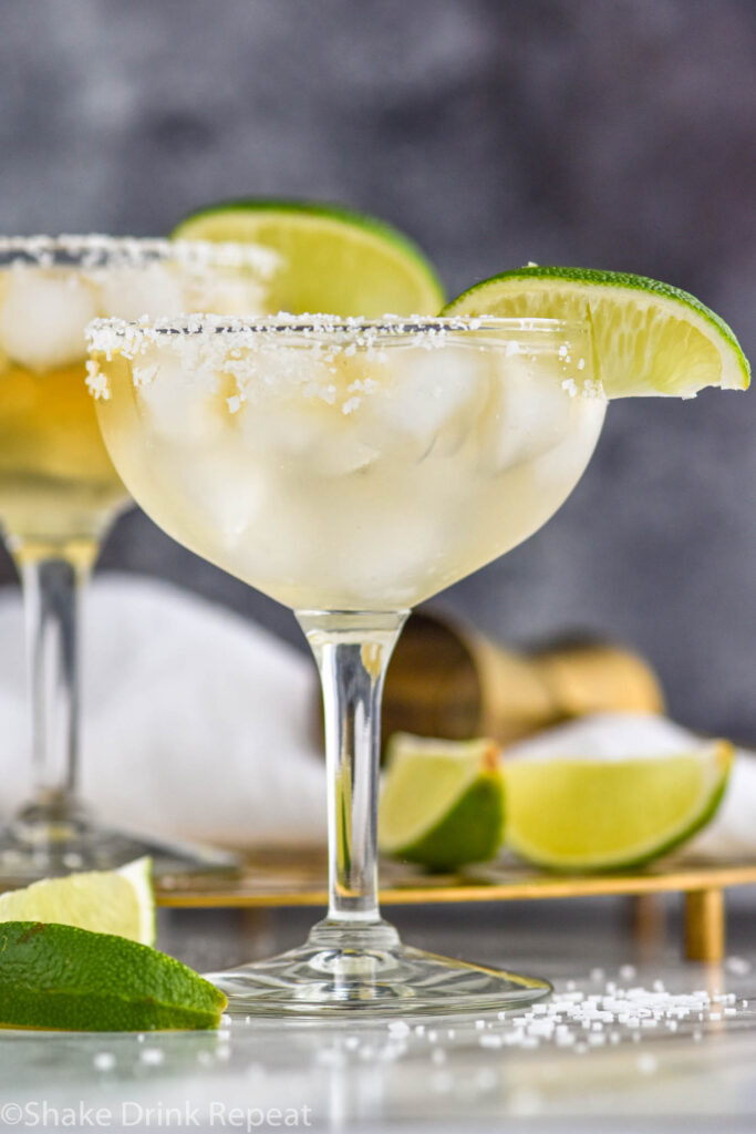 two glasses of Cadillac Margarita with salted rim, ice, and lime wedge garnish