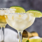 two glasses Cadillac Margarita with ice, salted rim, and lime wedge garnish
