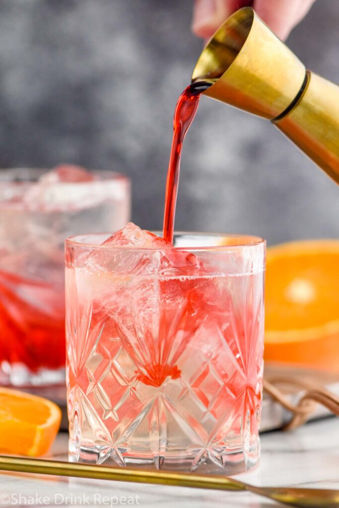 man's hand pouring jigger of grenadine into a glass of cherry vodka soda and ice surrounded by a spoon and fresh orange slices