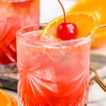 two glasses of cherry vodka sour with ice, orange slice and cherry garnish