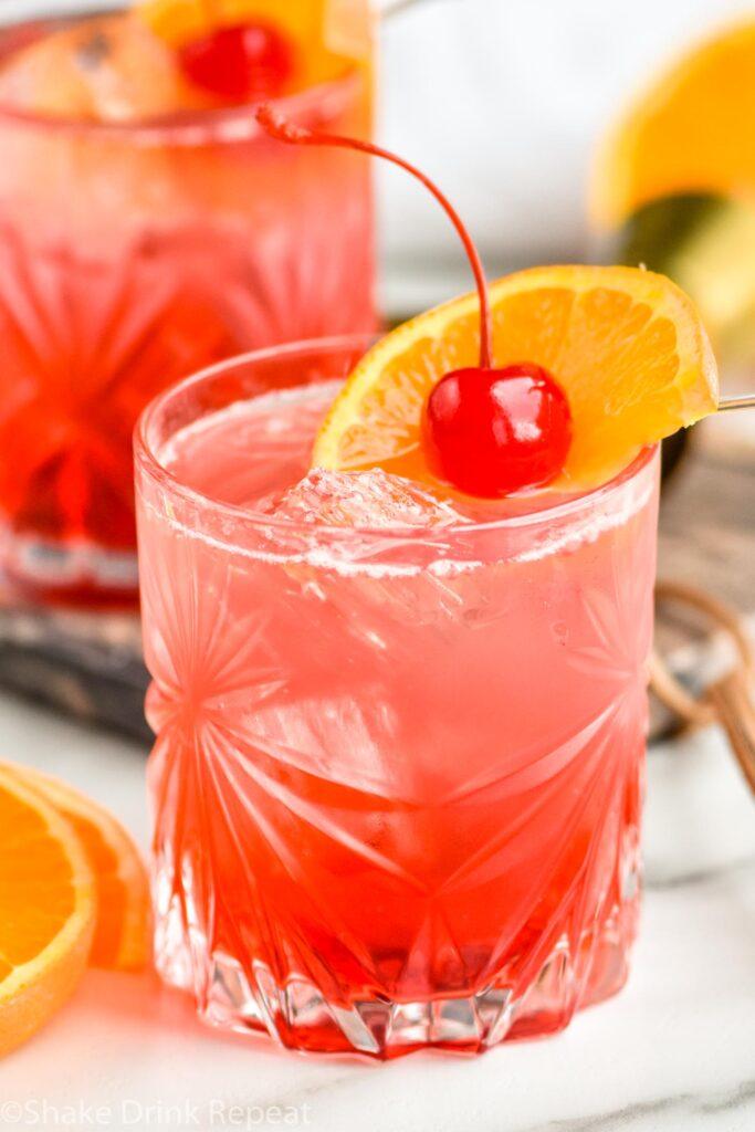 two glasses of cherry vodka soda with ice, orange slice and cherry garnish