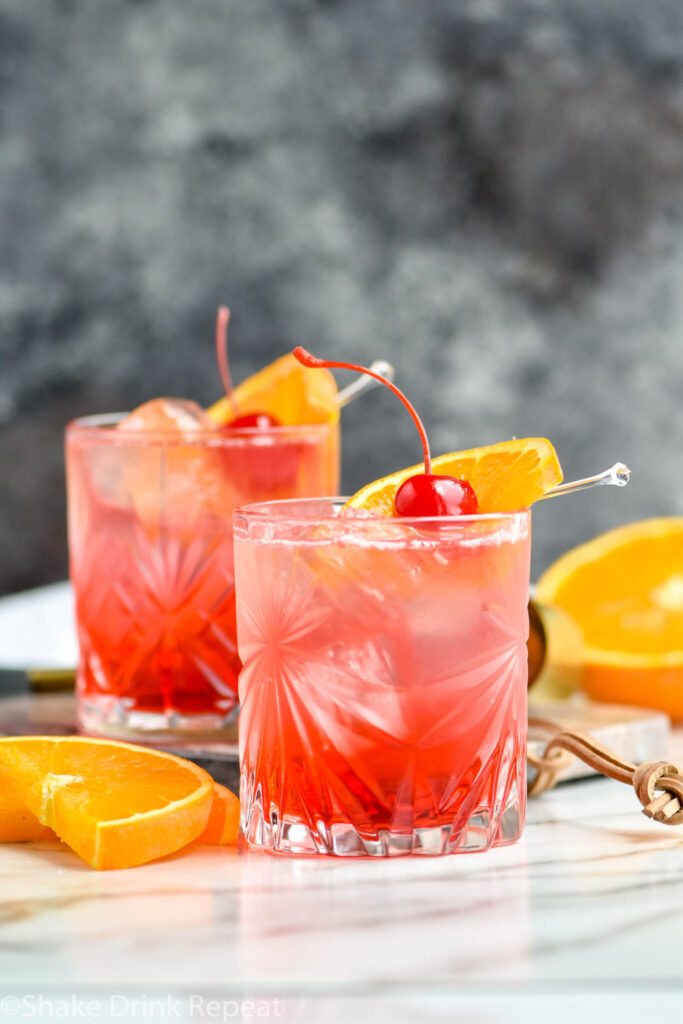 two glasses of Cherry Vodka Sour with ice and an orange slice and cherry garnish