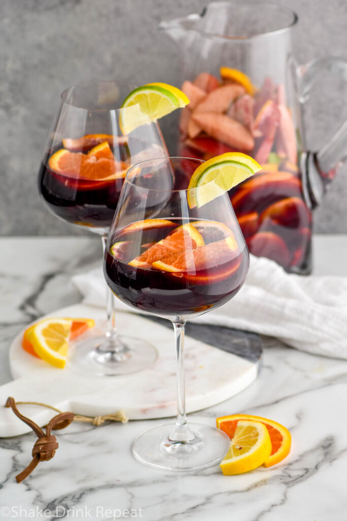 pitcher and two glasses of red sangria with fresh fruit including slices of lemons, limes, and oranges