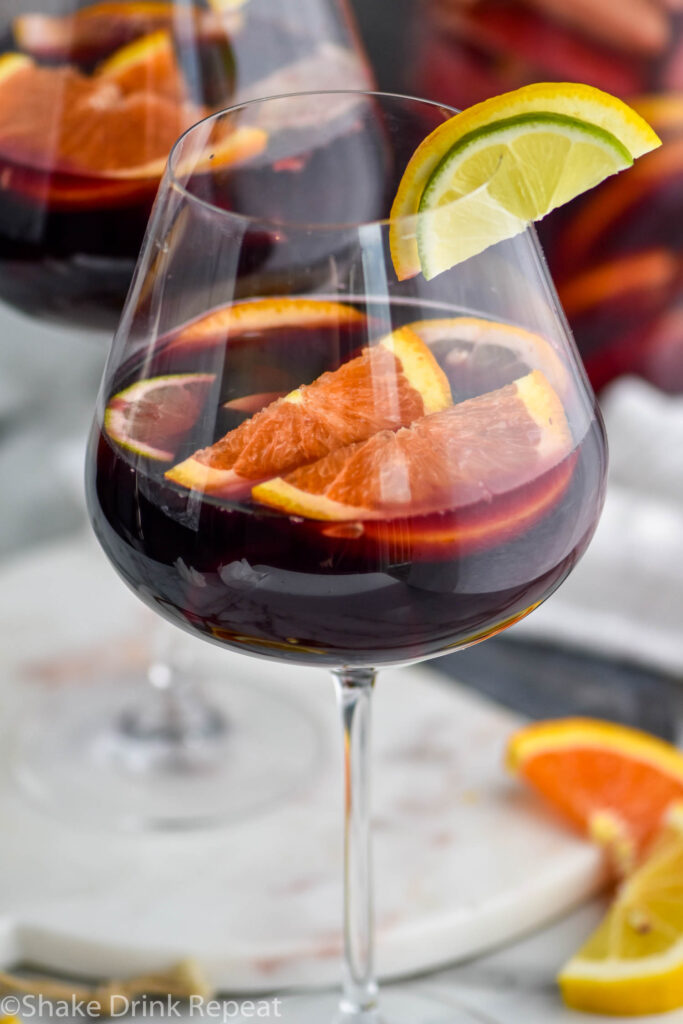 glass of red sangria with slices of fresh fruit including lemons, limes, and oranges