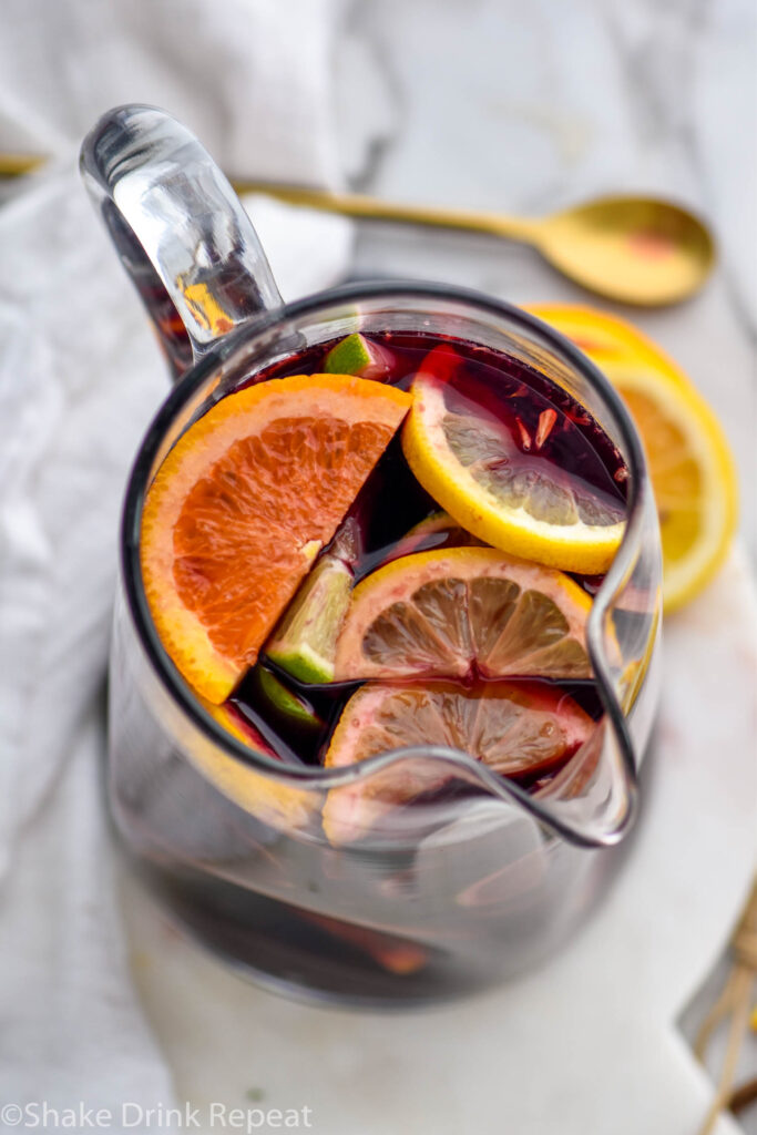 pitcher of red sangria with slices of fresh fruit including lemons, limes, ad oranges