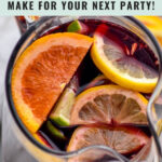 pitcher of red sangria with slices of fresh lemons, limes, and oranges