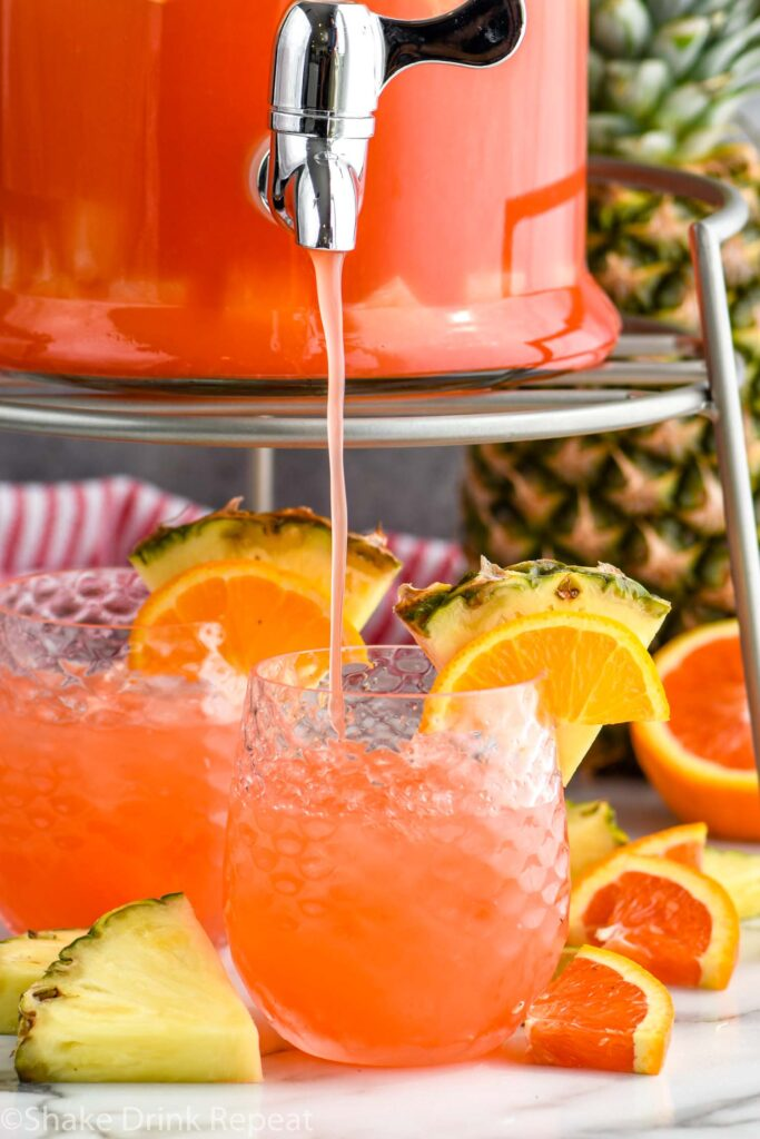 Glass dispenser of of rum punch pouring into a glass of ice with fresh pineapple and orange slices