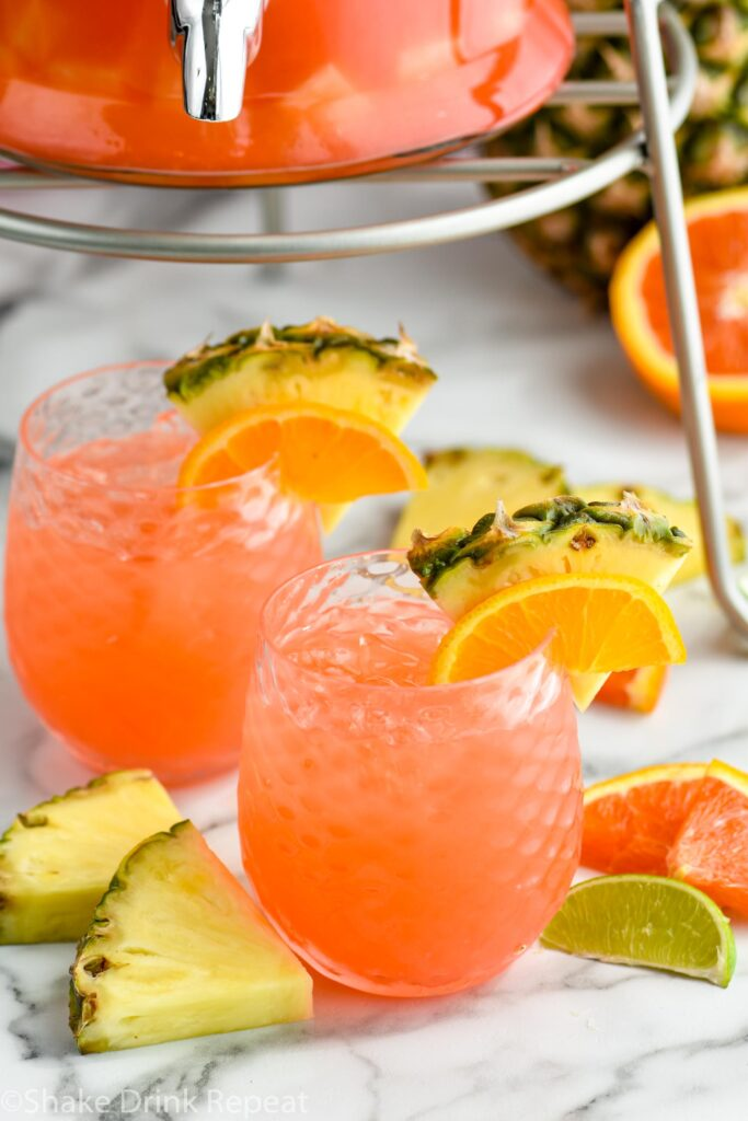 two glasses of rum punch with ice, fresh pineapple, orange slices, and lime