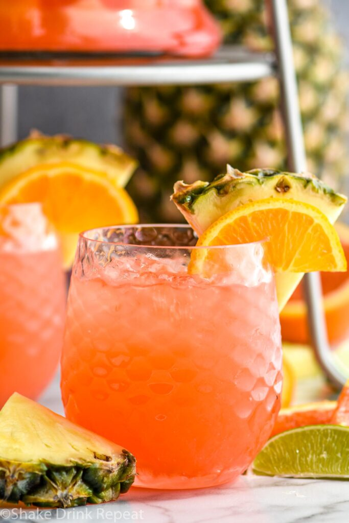 glass of rum punch with ice, slices of pineapple, orange, and lime