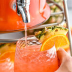 man holding a glass of ice filling with rum punch with fresh pineapple and orange