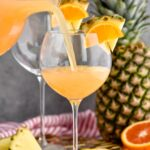 pitcher of tropical sangria pouring into glass garnished with slices of fresh pineapple and orange