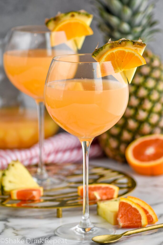 two glasses of tropical sangria with slices of fresh pineapple and oranges