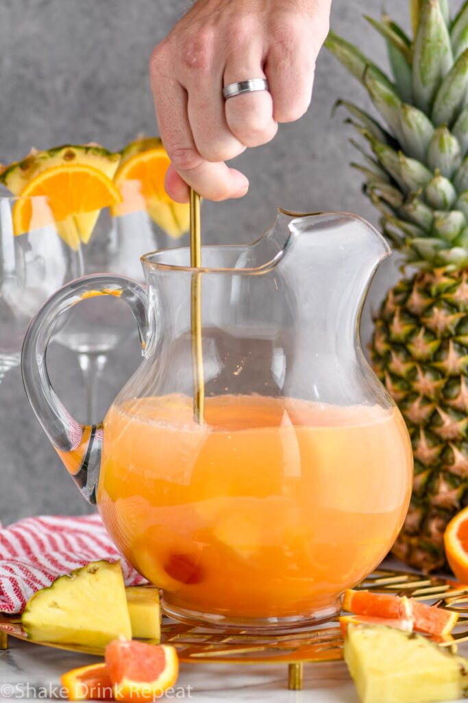 man's hand stirring pitcher of tropical sangria surrounded by slices of fresh pineapple and oranges