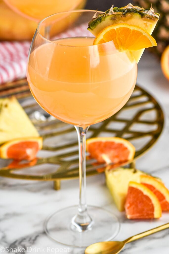 glass of tropical sangria with slices of fresh pineapple and oranges
