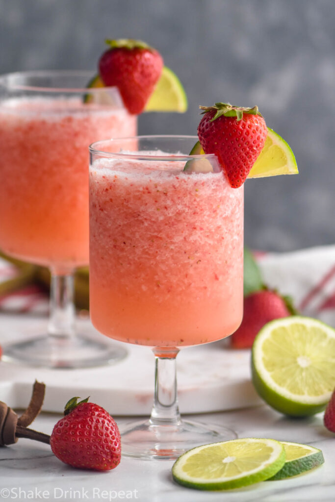 two glasses of virgin strawberry daiquiri with fresh strawberries and lime garnish
