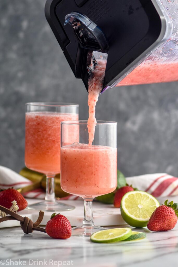 blender of virgin strawberry daiquiri poured into a cocktail glass surrounded by fresh strawberries and limes