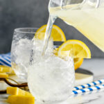 man pouring pitcher of lemonade into a glass of vodka and ice with lemon garnish
