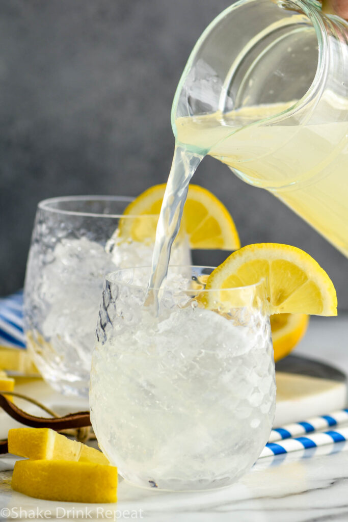 pouring pitcher of lemonade into a glass filled with ice and vodka to make a vodka lemonade with slices of lemon for garnish