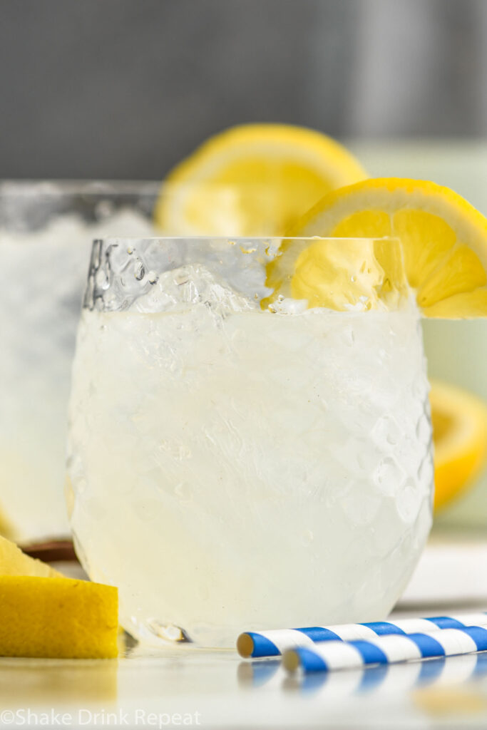 two glasses of vodka lemonade with ice, straws, and lemon slices