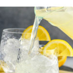 pouring lemonade into a glass of ice to make a vodka lemonade with lemon garnish