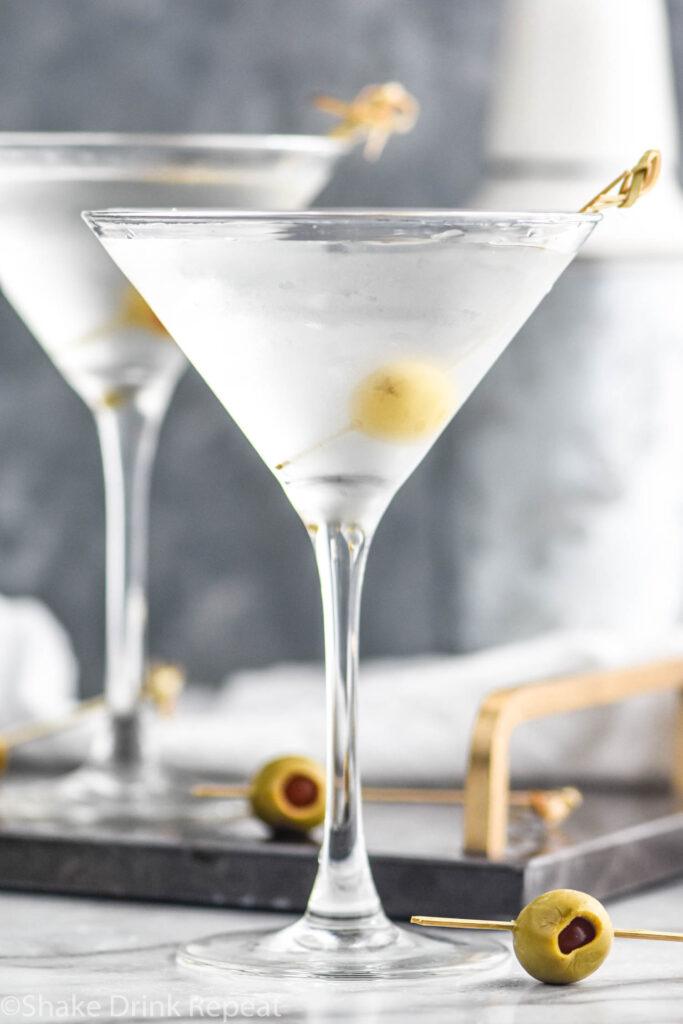two glasses of vodka martini with olive garnish