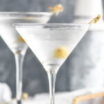 two chilled martini glasses of vodka martini with olive garnish