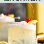 glass of vodka sour with frothy egg white and slice of lemon and cherry garnish with spoon in front