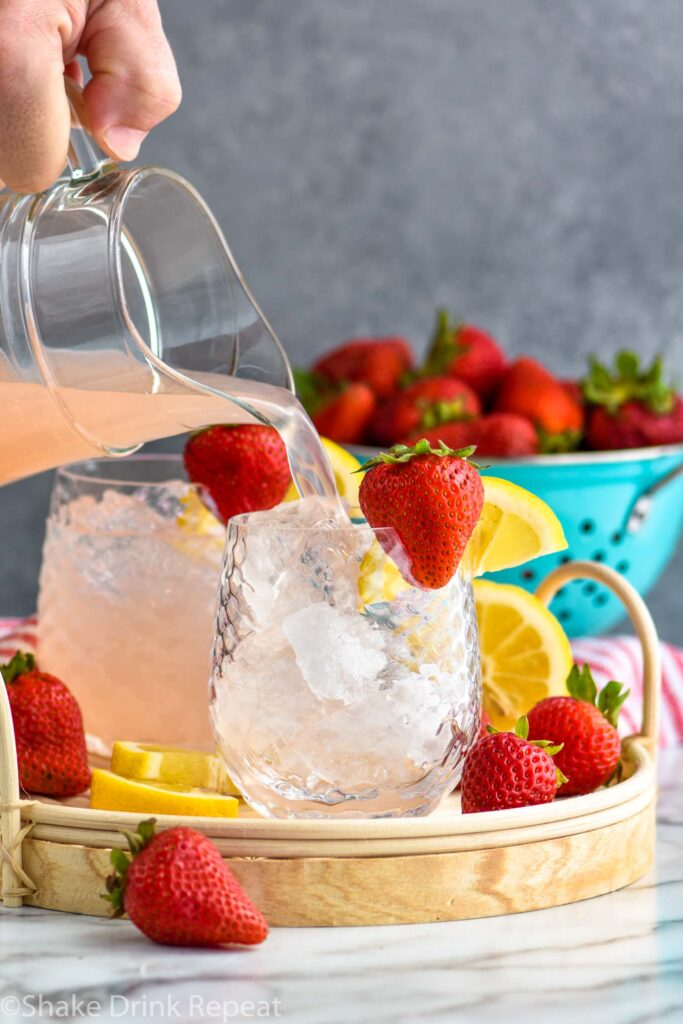 man pouring a pitcher of vodka strawberry lemonade into a glass of ice with fresh strawberries and lemon slices