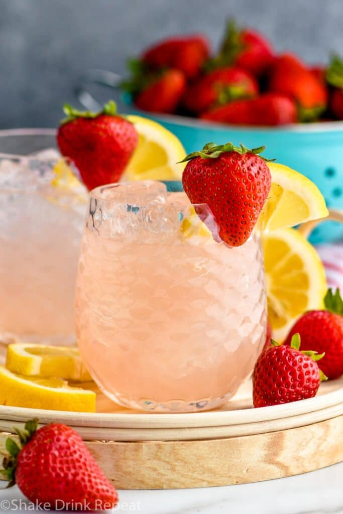 two glasses of vodka strawberry lemonade with ice, strawberries and lemon slices