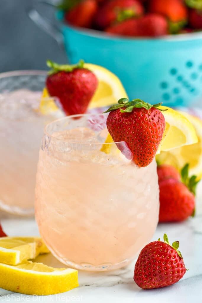 two glasses of vodka strawberry lemonade with ice, fresh strawberries, and lemon slices