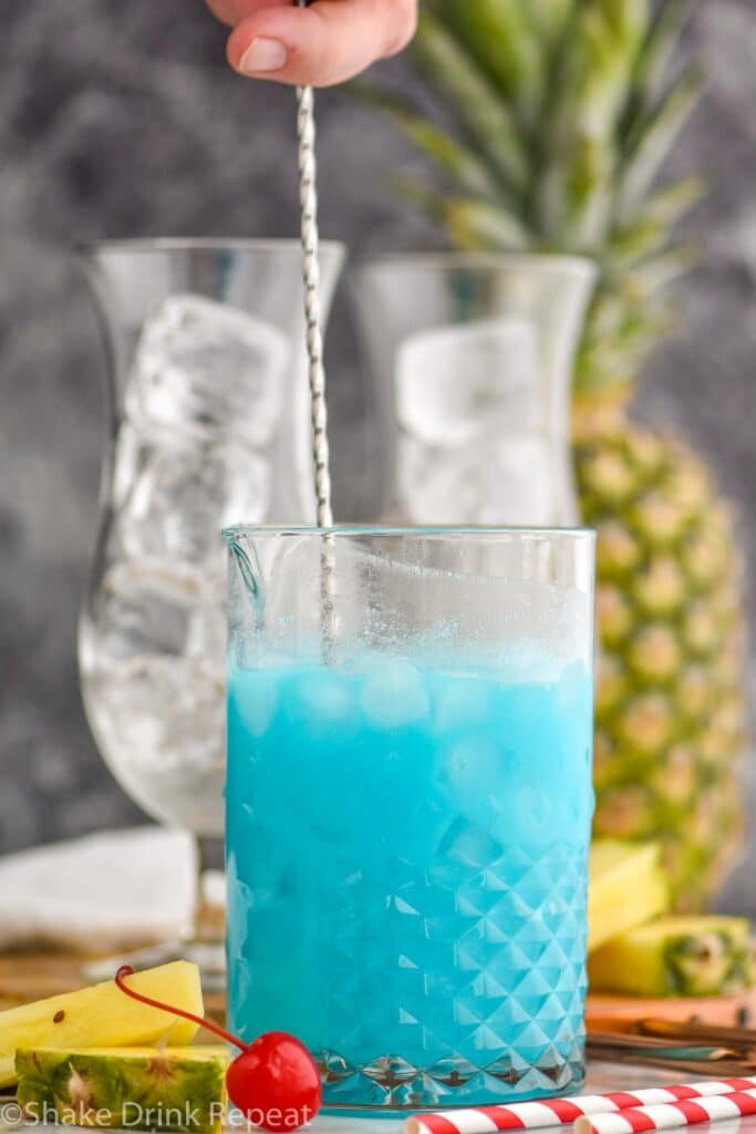man stirring ingredients of blue hawaiian in a glass with ice surrounded by straws, fresh pineapple and cherries
