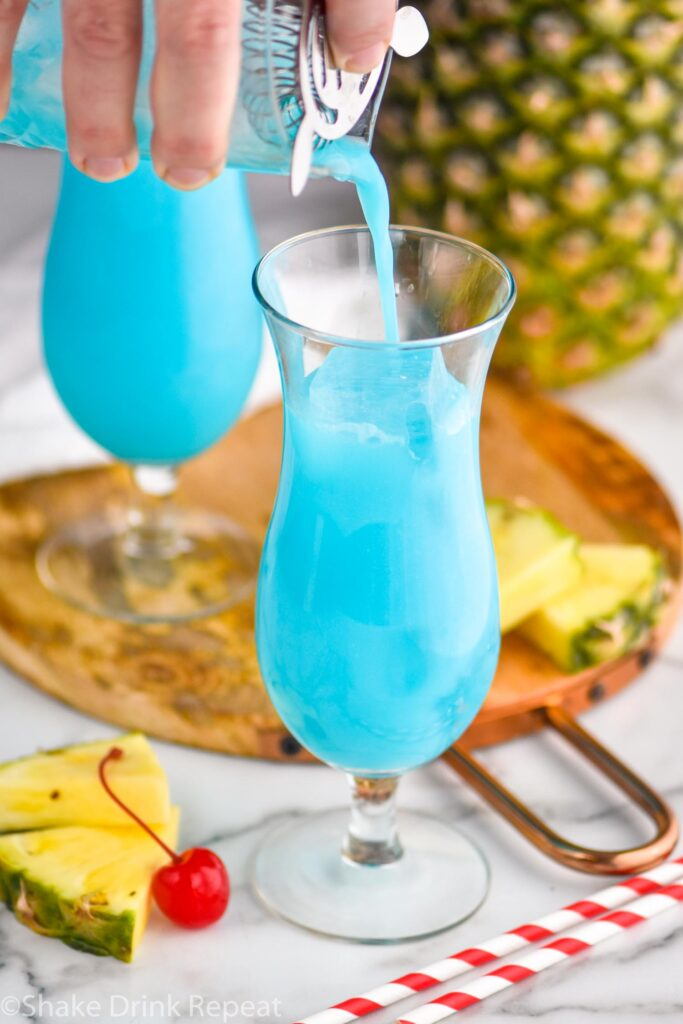 man pouring blue hawaiian ingredients from a shaker into a glass filled with ice surrounded by straws, fresh pineapple wedges and cherries.