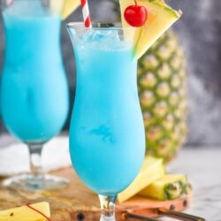 two glasses of blue hawaiian with ice, straws, cherries, and fresh pineapple wedge garnish