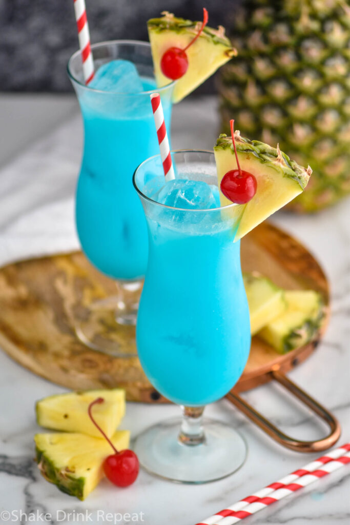 two glasses of blue hawaiian with ice, straws, cherries, and wedges of fresh pineapple