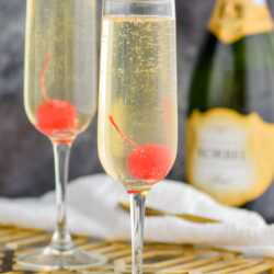 two glasses of french 76 garnished with a cherry with bottle of champagne, cork, and spoon in the background
