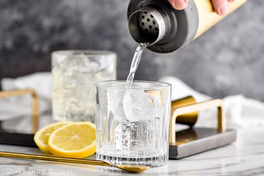 man pouring shaker of vodka sour ingredients into a rocks glass filled with ice surrounded by fresh lemon slices and a spoon