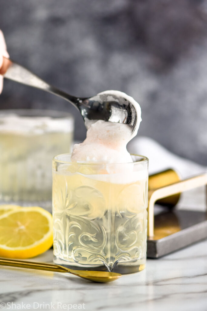 spoon of frothy egg white adding to the top of a glass of vodka sour surrounded by spoon and fresh lemon