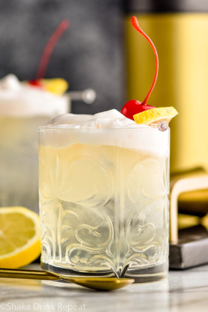 two glasses of vodka sour with lemon and cherry garnish