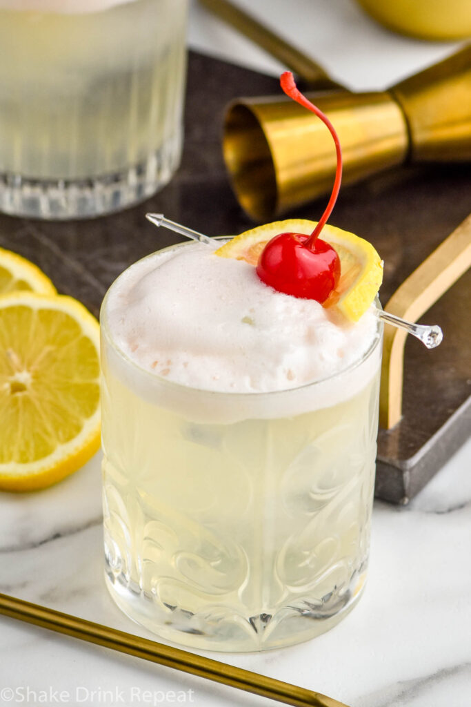 glass of vodka sour with fresh lemon slices and cherry garnish